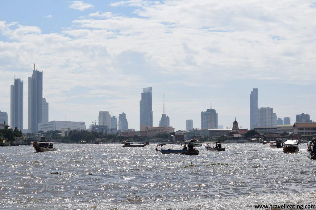 Río Phraya repleto de barcas tradicionales y la ciudad de Bangkok al fondo. Otro de los imprescindibles de Bangkok.