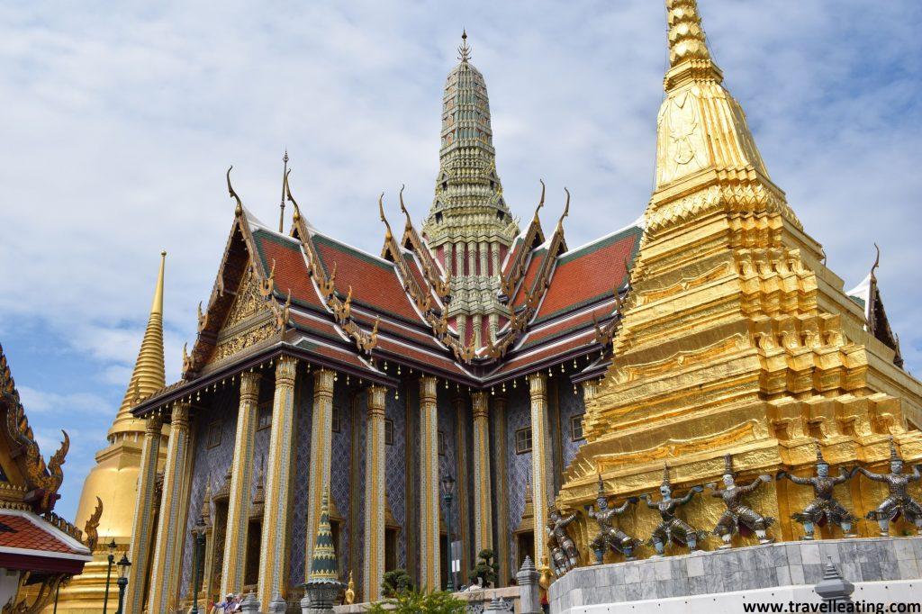 Primer plano de una pagoda piramidal dorada que ocupa la parte derecha de la imagen y a su izquierda vemos de fondo uno de los edificios más bonitos del Gran Palacio de Bangkok.
