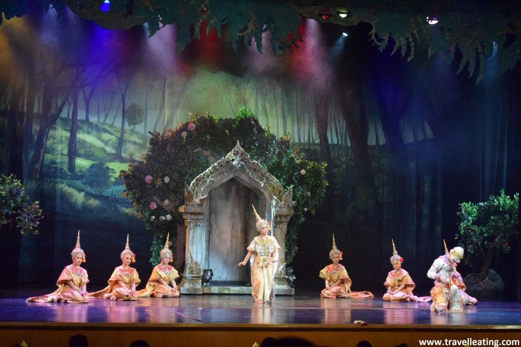 Escena de una representación de teatro en la que vemos unas mujeres encima de un escenario vestidas con trajes tradicionales tailandeses bailando.