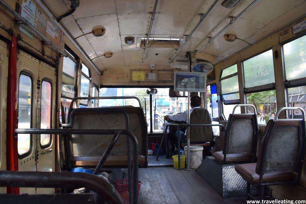 Interior de un autobús local de Bangkok el cual va prácticamente vacío. Es de color grisáceo todo él.