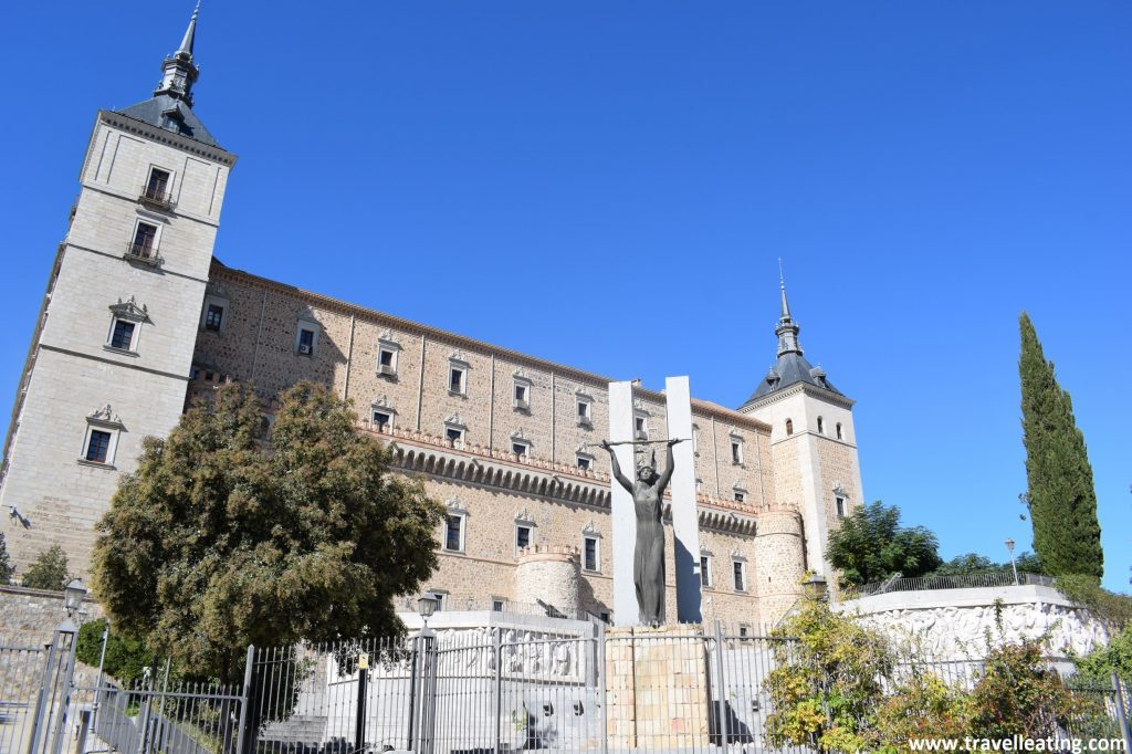 Edificio del Alcázar de Toledo con una estatua en frente de una mujer sujetando una espada con las manos alzadas.