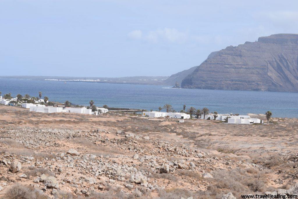 Precioso pueblo blanco, formado por casas tradicionales canarias con las puertas y ventanales verdes, rodeadas de palmeras rodeado de paisaje desértico por un lado y del mar por el otro. Al fondo, se ve la isla de Lanzarote.