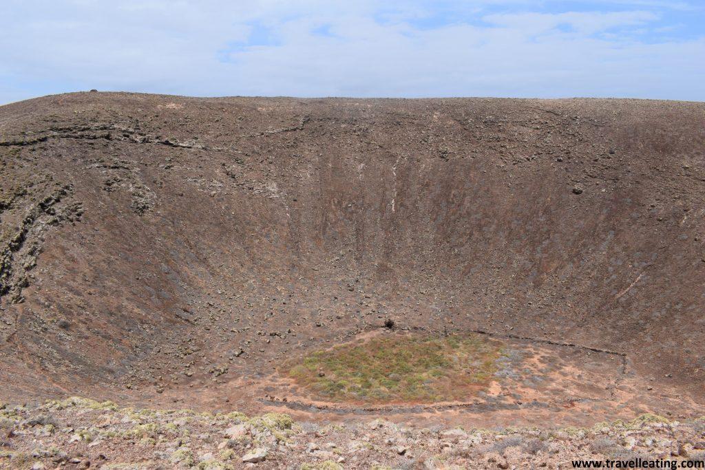 Vistas del interior del cráter de un volcán. En su zona central destaca una zona verde repleta de vegetación, a diferencia del resto que es todo material volcánico.