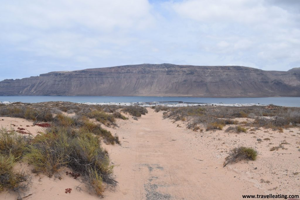 Camino de tierra entre dunas al fondo del cual se visualiza un pueblo blanco, Caleta de Sebo, uno de los núcleos urbanos de la Isla de la Graciosa. Tras éste, vemos el mar y Lanzarote, con su imponente risco.