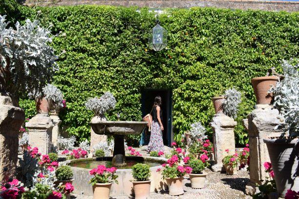 Patio con una fuente en medio, rodeada de torres de mármol con flores encima y tras la cual destaca una pared repleta de hojas verdes de enredadera.
