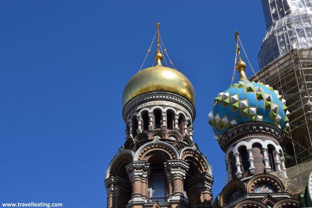 Primer plano de dos cúpulas de la Iglesia del Salvador sobre la Sangre Derramada. Una de ellas dorada y la otra azul cielo con relieves blancos y verdes.