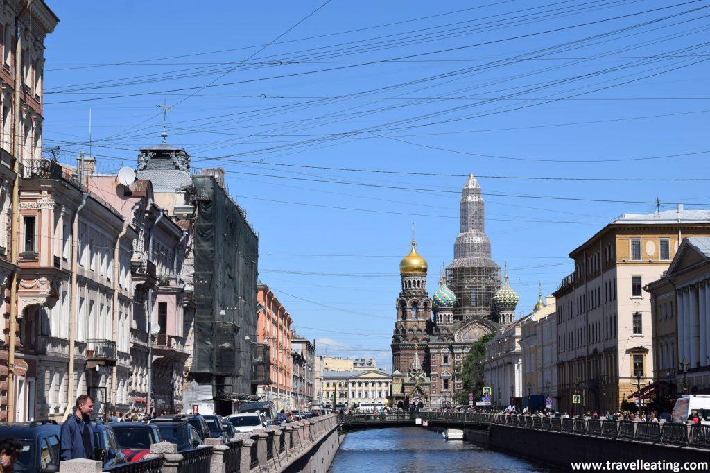 En la foto se ve un canal en medio de una ciudad desde y está tomada desde uno de los puentes. A orillas de éste, al fondo a la derecha, se aprecia la figura de la catedral más popular de la ciudad, con sus cúpulas. La del medio recubierta en andamios por eso.