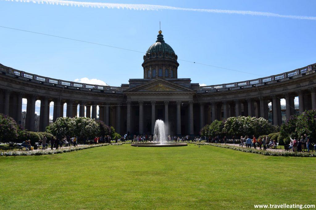 Catedral de Kazán, con su fachada en forma semicircular y su increíble columnata. Delante de ésta hay un parque verde repleto de césped con algunos árboles floridos alrededor y una fuente en medio. Otro de los imprescindibles que ver en San Petersburgo