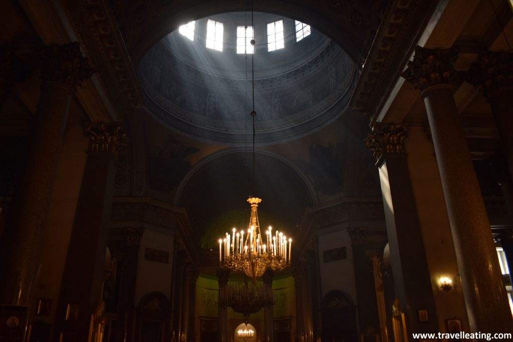 Interior de la Catedral de Kazán. Éste es bastante oscuro pero por las ventanas de la bóveda central (que corresponden a la cúpula) se cuelan unos rayos de luz hacia creando unos haces de luz muy particulares. En el centro de ésta encontramos una gran lámpara dorada repleta de velas de cristal.