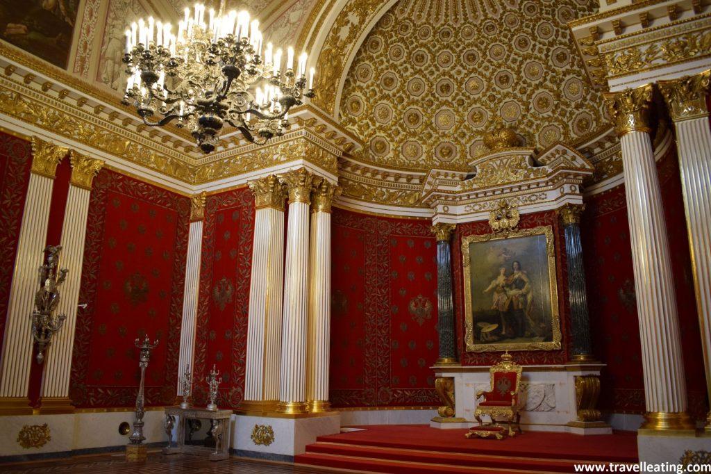 Una de las salas del Museo Hermitage que destaca por tener un trono en la parte central con un cuadro detrás. Las paredes de la sala son rojas, con columnas blancas y doradas, y el techo en cambio es blanco con relieves dorados. En el centro de la sala una gran lámpara de cristal la ilumina.