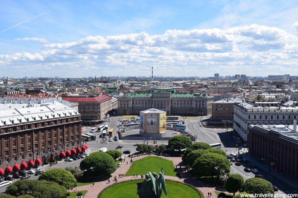 Vistas de la ciudad de San Petersburgo des del mirador de la cúpula de la Catedral de San Isaac. En el centro vemos una plaza con un parque verde y alrededor se estructuran las diferentes manzanas. El cielo está abierto, con unas nubes muy esponjosas que lo adornan.