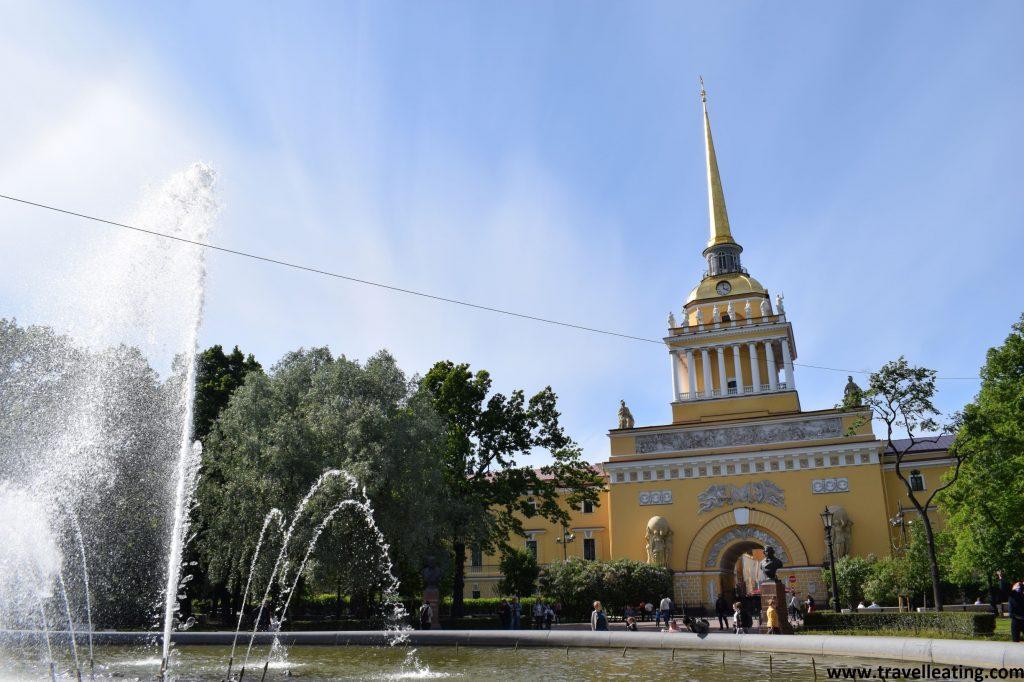 Plaza del centro de la ciudad, con un edificio amarillo con una torre de reloj y una fuente delante.