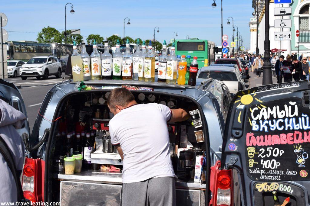 Vemos la parte trasera de una furgoneta con las puertas abierta y dentro del maletero una máquina de hacer cafés y todo de bebidas expuestas. Hay un hombre de espaldas sirviendo una bebida, y en la puerta el cartel con los precios.