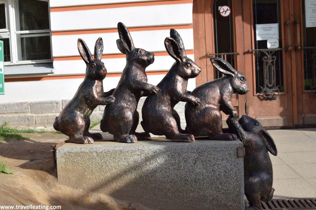 Aparecen 4 graciosos conejos en línea, uno detrás del otro, cogiéndose encima de una piedra, y al final uno colgando, como a punto de caer, al cual están cogiendo. La escultura es de bronce, no muy grande.