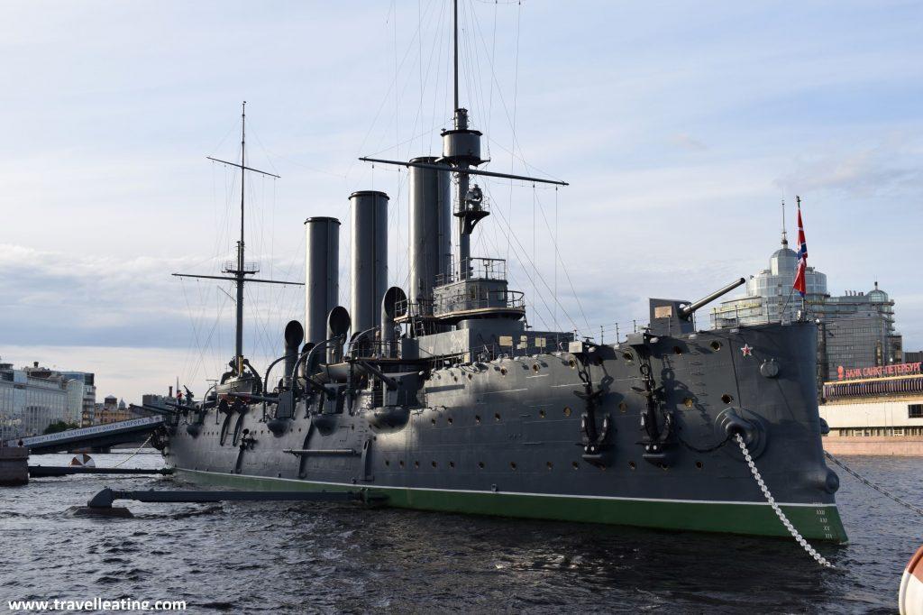 Nave militar de color verde kaki que se encuentra amarrada en las orilla del río Neva. En su lateral destacan dos enormes anclas y las armas de guerra, para disparar misiles y otros.