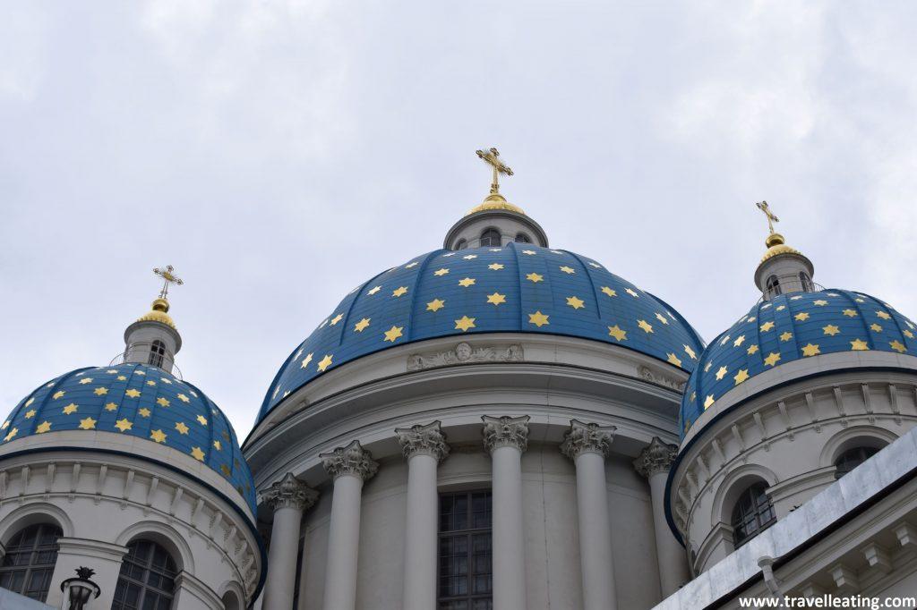 Primer plano de las cúpulas de la Catedral de la Santa Trinidad, de San Petersburgo. De azul intenso con estrellas doradas decorándolas. Y coronándolas, arriba de cada una, una cruz dorada.
