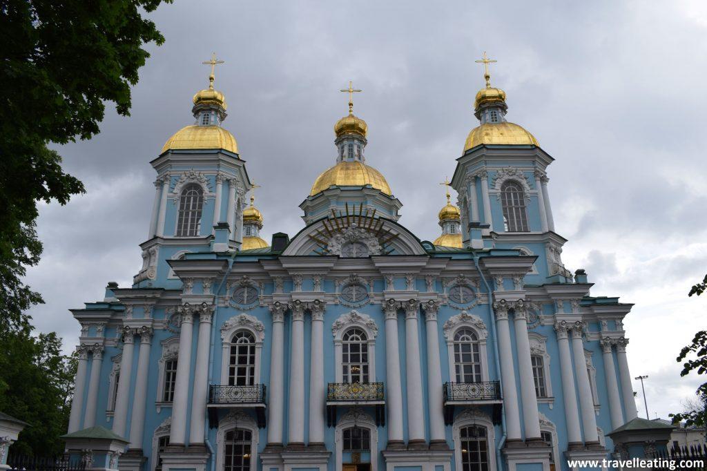 Fachada Principal de la Iglesia de San Nicolás. Una iglesia azul celeste, de estilo ortodoca con las columnas y otros detalles blancos. Presenta también 5 cúpulas doradas acabadas en una cruz.