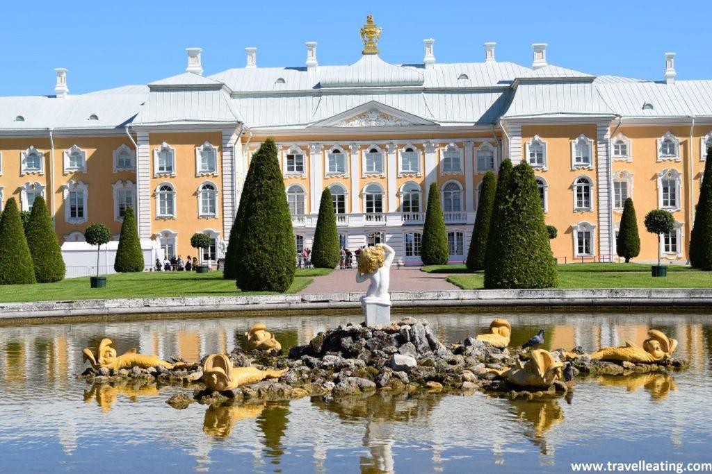 En la foto vemos la fachada principal del Palacio Peterhof, de color amarillo pastel y azul muy claro. Delante de él luce un camino franqueado por setos y delante de éste, una hermosa fuente con esculturas en medio. Uno de los lugares imprescindibles de ver en las afueras de San Petersburgo.