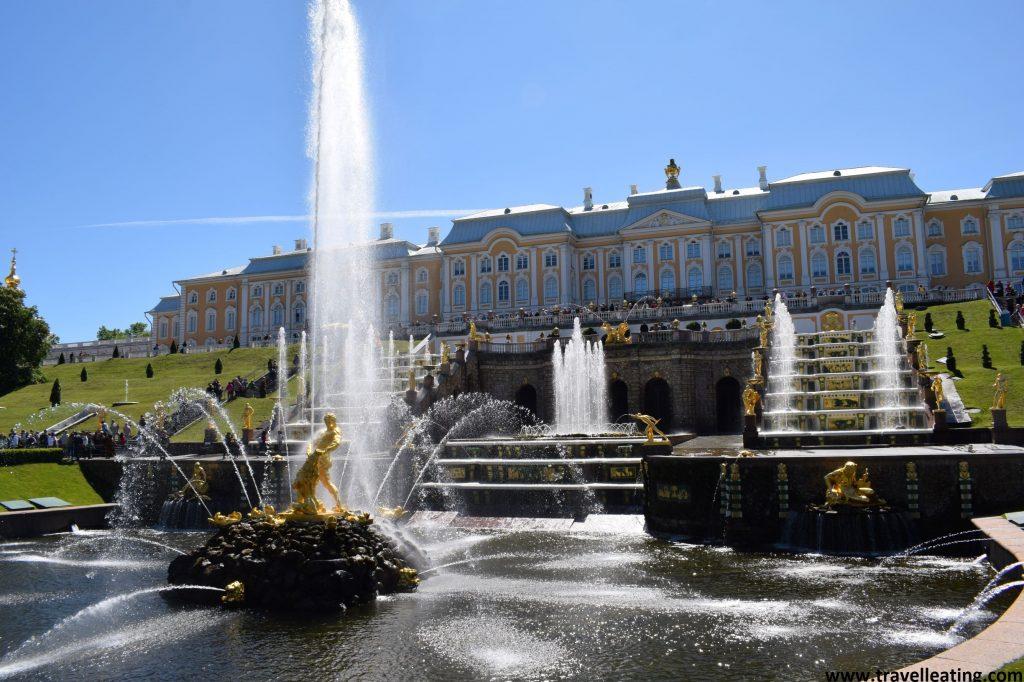 Fuente muy grande con una escultura en medio, junto al chorro de agua, y muchas terrazas detrás con más subfuentes y muchas más esculturas de oro. Al fondo vemos la fachada principal del bonito Palacio Peterhof.