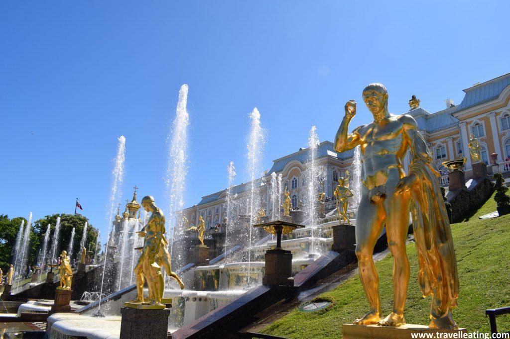 Gran fuente estructurada en cascada y repleta de esculturas doradas frente la fachada principal del Palacio Peterhof,, que a penas se ve pues queda tapada por la agua que se eleva de ésta.