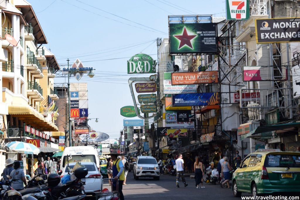 Calle comercial del centro de Bangkok con decenas de carteles de restaurantes y bares, tiendas y otros comercios. La calle además está repleta de gente y coches. Otro de los imprescindibles de Bangkok.