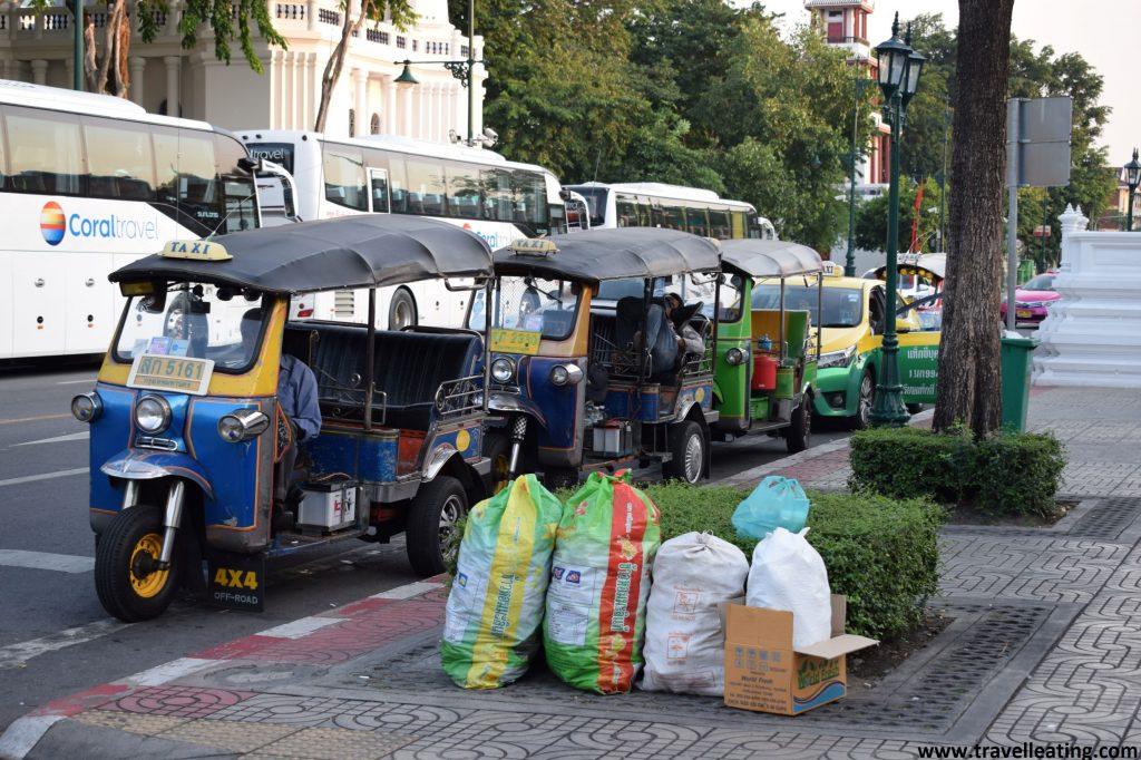 tres tuk-tuk azules y amarillos en fila en una calle de Bangkok.