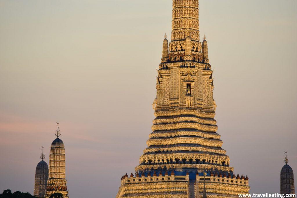 primer plano de la torre principal del templo iluminada de noche. Ésta se ve dorada, y tras ella vemos un cielo rojizo por la puesta del sol.