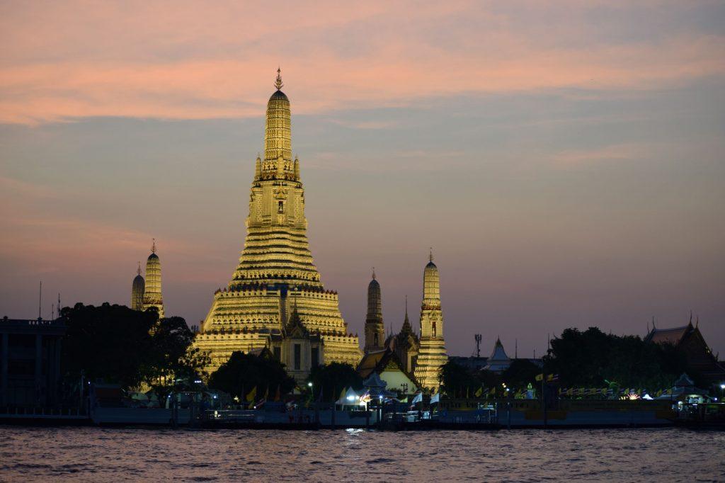 Templo Wat Arun iluminado frente al río durante la puesta de sol.
