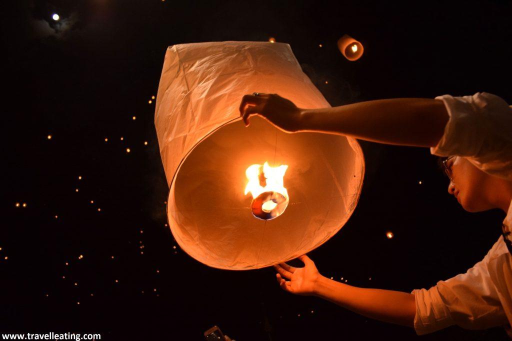 Brazos sujetando una linterna encendida con fuego, casi preparada para dejarla ir. La imagen se ve desde abajo de manera que alrededor se ve el cielo negro con lucecitas que corresponden a los farolillos ya soltados al cielo.