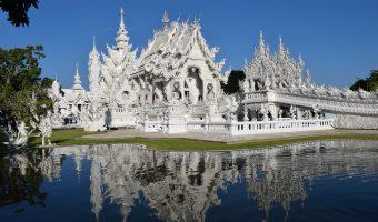 Impresionante templo blanco situado frente a un pequeño estanque en el cual se refleja su imagen.