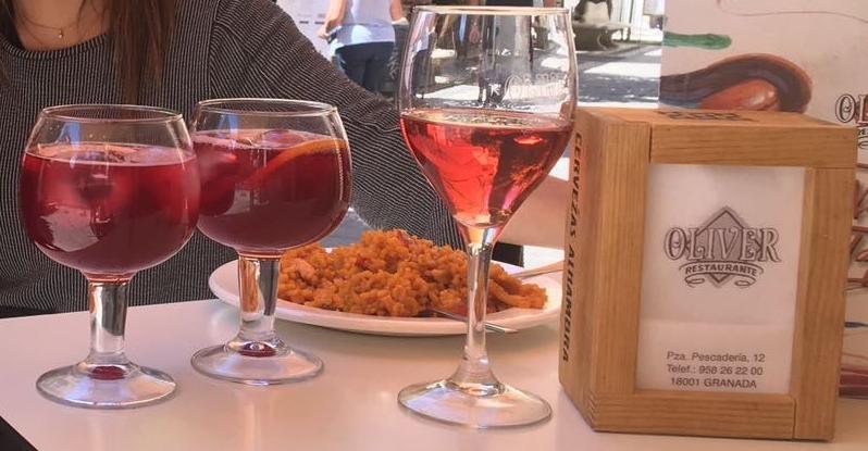 Tintos de verano acompañados de una tapa de arroz en la mesa de una terraza.