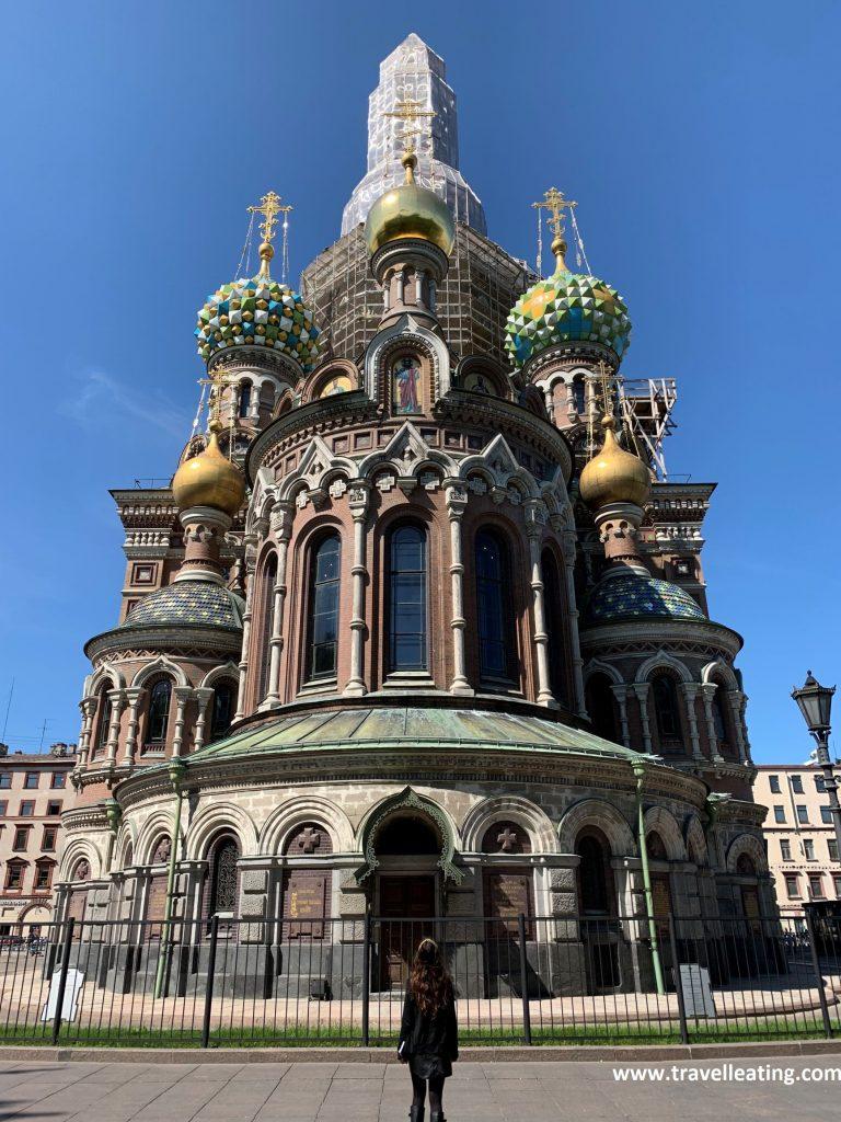 Preciosa fachada lateral de la Iglesia del Salvador sobre la Sangre Derramada con una chica de espaldas, mirándola. La parta central de arriba está cubierta de andamios, pero las cúpulas doradas y de colores consiguen que siga siendo impresionante. Es uno de los imprescindibles que ver en San Petersburgo.