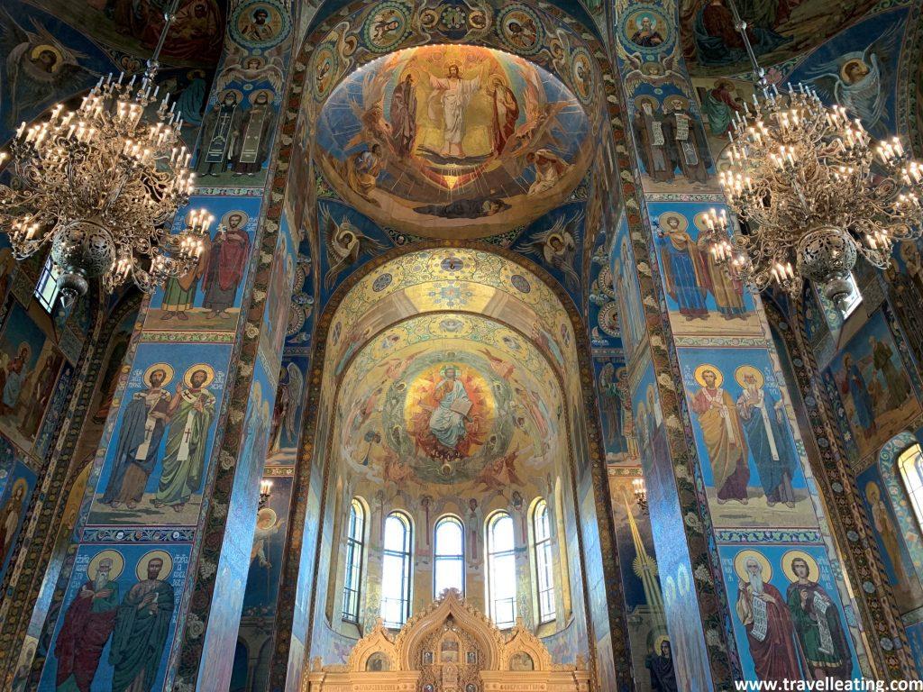 Interior de la Iglesia del Salvador sobre la Sangre Derramada. Las paredes están recubiertas de murales azules con imágenes sagradas donde predomina el color dorado. Dos espectaculares lámparas se alzan a cada lado de la imagen.