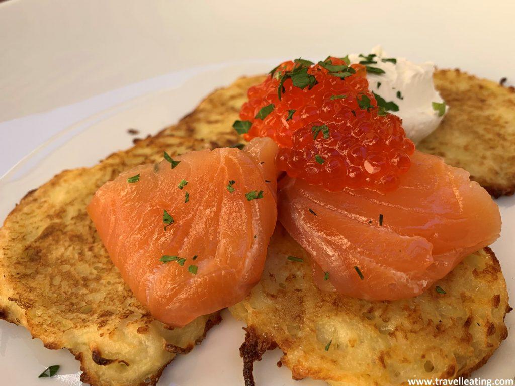 Pequeñas creps esponjosas con salmón, huevas de salmón y crema agria por encima.