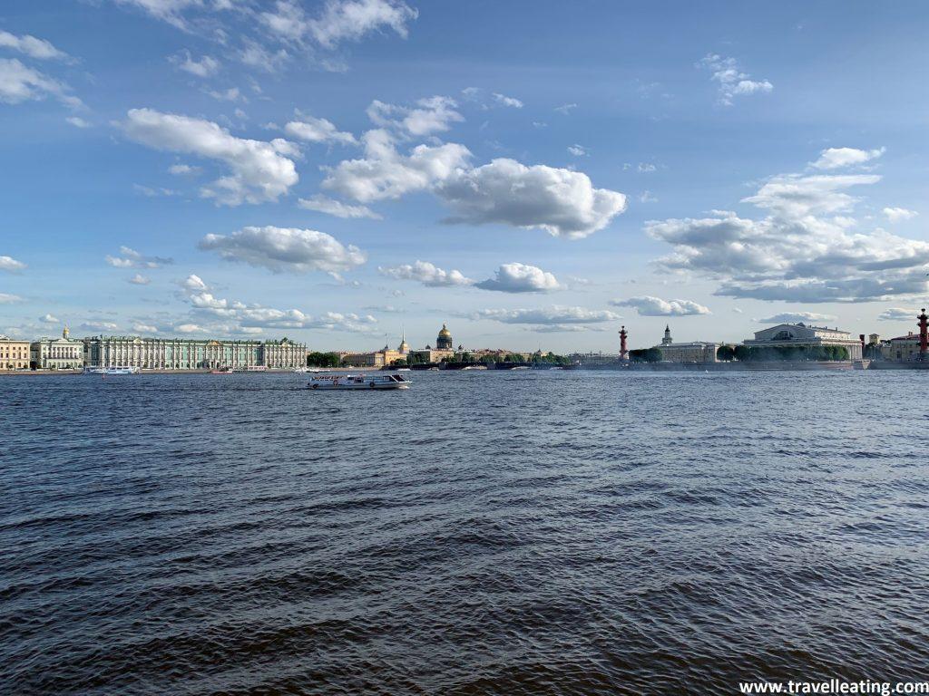 Imagen del gran río Neva con un barco cruzándolo. Al fondo vemos el bonito edificio del Palacio de Invierno (el Museo Hermitage), a orillas de éste, y de entre la imagen del centro de la ciudad también destaca la cúpula dorada de la Catedral de San Isaac.