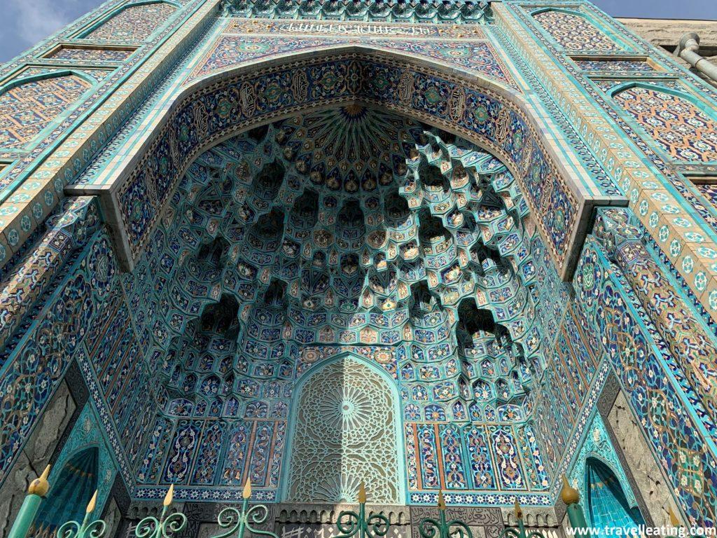 Imagen de la entrada principal de la mezquita. Toda ella es azul, repleta de relieves que mezclan diferentes tonos de azul con el blanco, dibujando diferentes motivos, algunos florales. El mosaico es realmente espectacular.