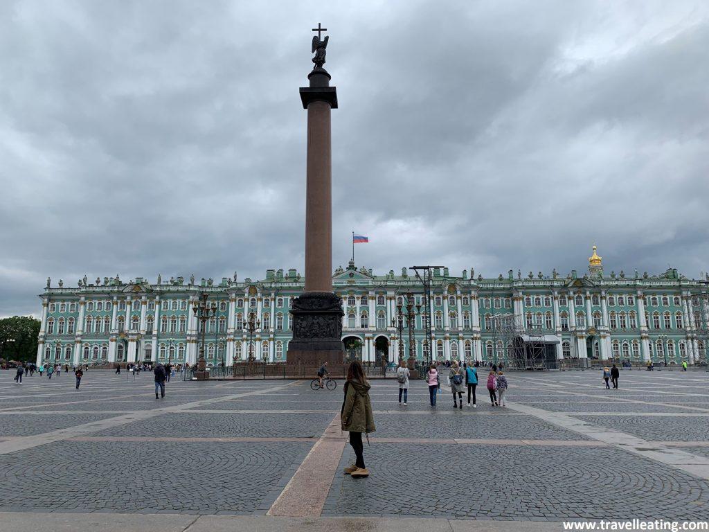 El otro lado de la Plaza Principal de San Petersburgo, donde tenemos la fachada principal del Palacio de Invierno (Museo Hermitage). Es un precioso edificio turquesa con columnas blancas que se ve en el fondo. Más adelante, en el centro de la foto hay un obelisco con una escultura que lleva una cruz encima. Y yo (Andrea) estoy en el medio de espalda, mirándolo todo.