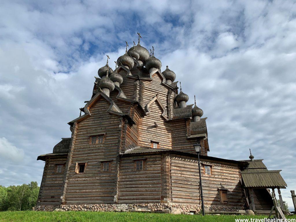 Iglesia ortodoxa de madera con cúpulas abombadas negras con escamas y acabadas en una cruz, que se alza encima de un prado verde. Se pueden ver 11 de las 25 cúpulas, las cuales se disponen como en triángulo, de arriba a abajo por los laterales. Uno de los imprescindibles que ver en las afueras de San Petersburgo.
