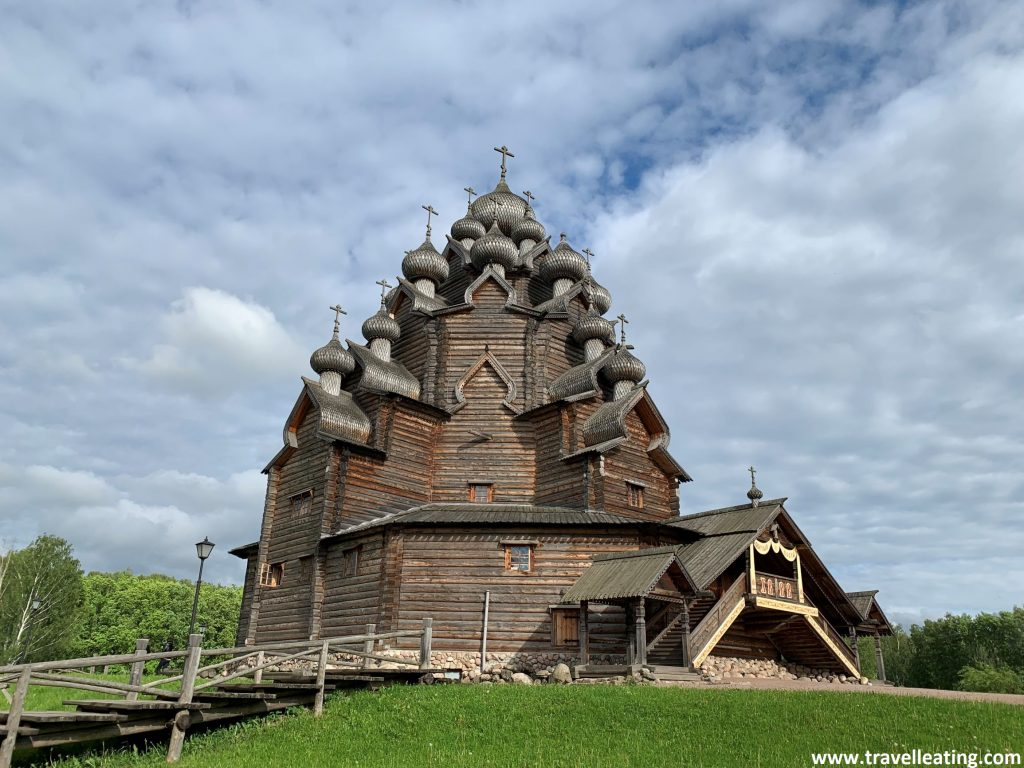 Iglesia ortodoxa de madera con cúpulas abombadas negras con escamas y acabadas en una cruz, que se alza encima de un prado verde. Se pueden ver 11 de las 25 cúpulas, las cuales se disponen como en triángulo, de arriba a abajo por los laterales.