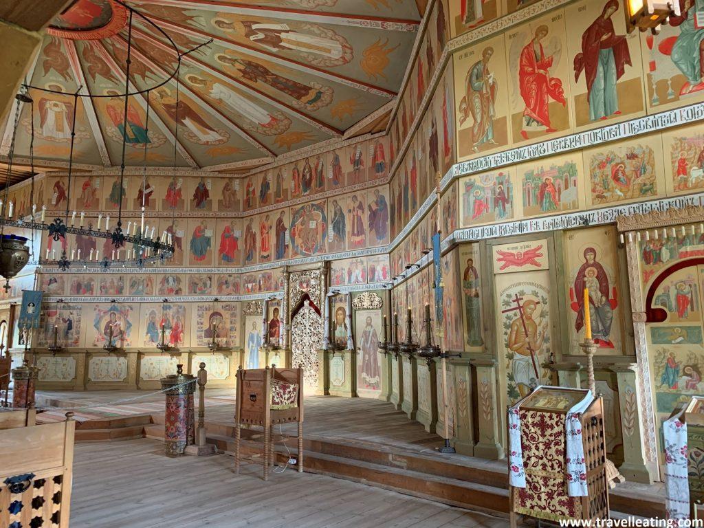 Otra imagen interior de la iglesia en la que se ven las paredes coloridas de ésta, repletas de imágenes religiosas separadas en rectángulos.