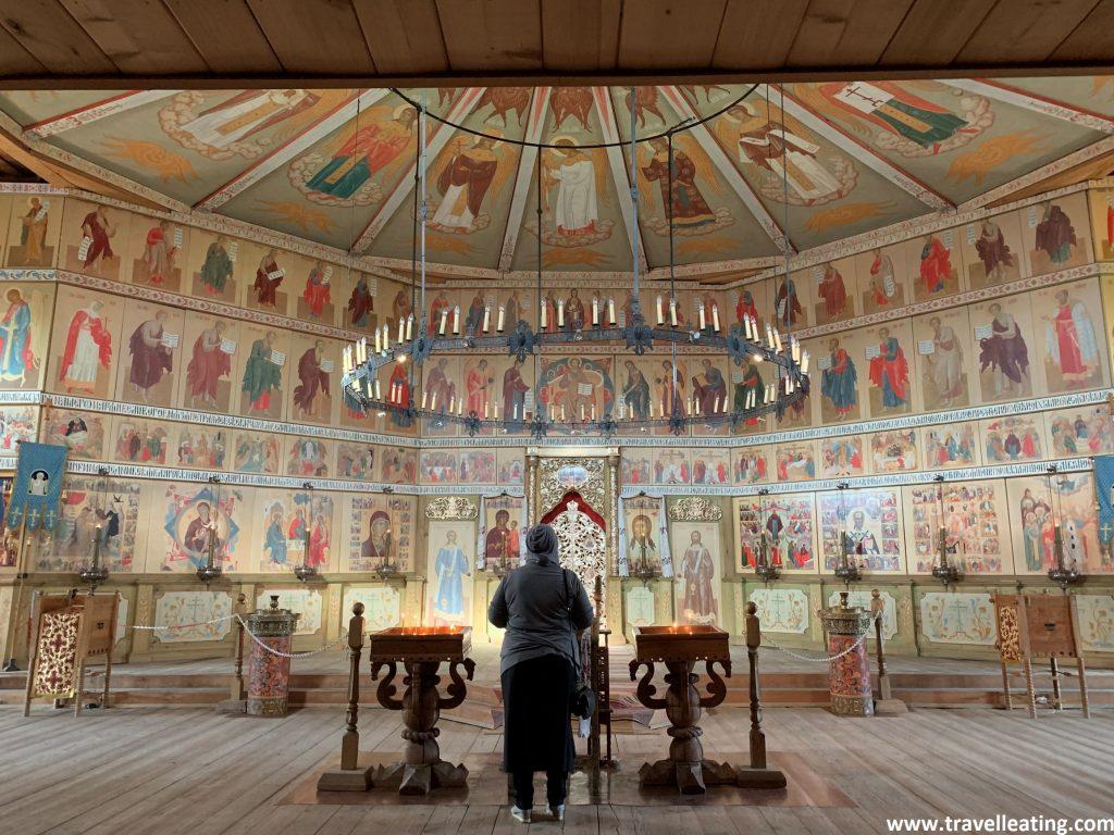 Altar de la iglesia la pared del cual está dividida en rectángulos y en cada uno de ellos encontramos una imagen religiosa. En el medio destaca un trono y una gran lámpara colgando del techo con centenares de velas. En un primer plano encontramos una señora de espaldas rezando, con el pelo cubierto y al lado con dos mesas repletas de velas.