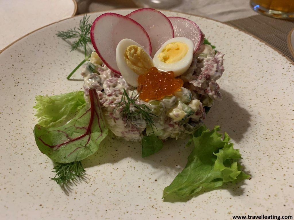 Ensaladilla con verduras troceadas y mayonesa la cual está servida formando como una torre circular con un huevo de codorniz partido en dos, rábanos troceados y huevas de salmón. Uno de los platos más típicos de la gastronomía rusa.