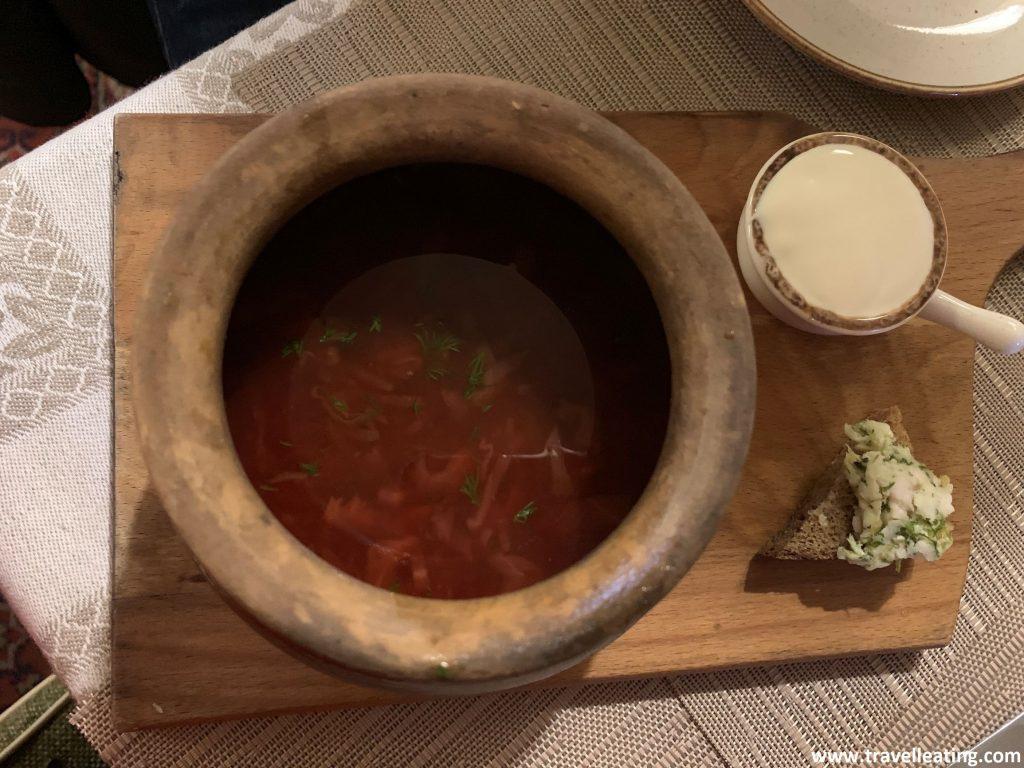 Cuenco de cerámica redondo que contiene una sopa rojiza, del color intenso de la berenjena. Al lado vemos un cuenco que contiene crema agria para hecharla a la sopa, y una mini tostada. Uno de los platos más típicos de la gastronomía rusa.