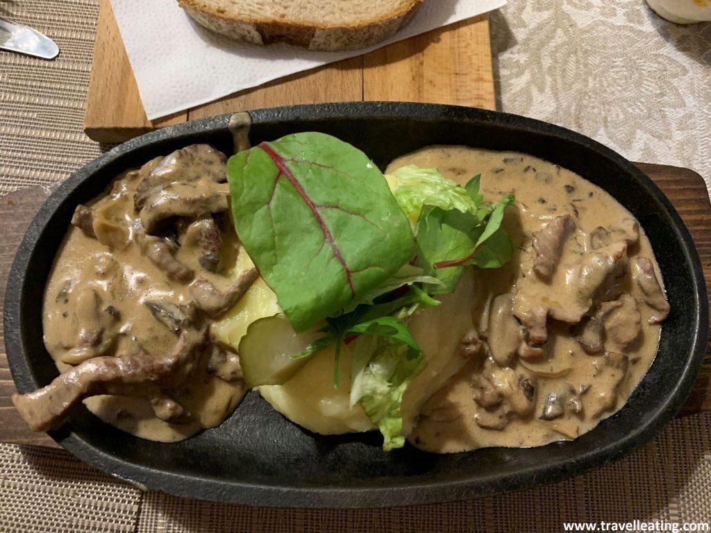 Plato en el que se observa carne de ternera hecha a tiras con salsa por encima donde se observan champiñones fileteados y cebollas pequeñas. Uno de los platos más típicos de la gastronomía rusa.
