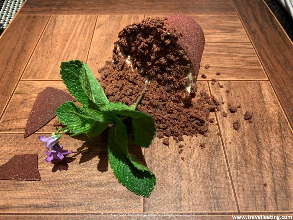 Tabla de madera sobre la cual vemos una maceta de chocolate volcada y rota con una flor comestible.