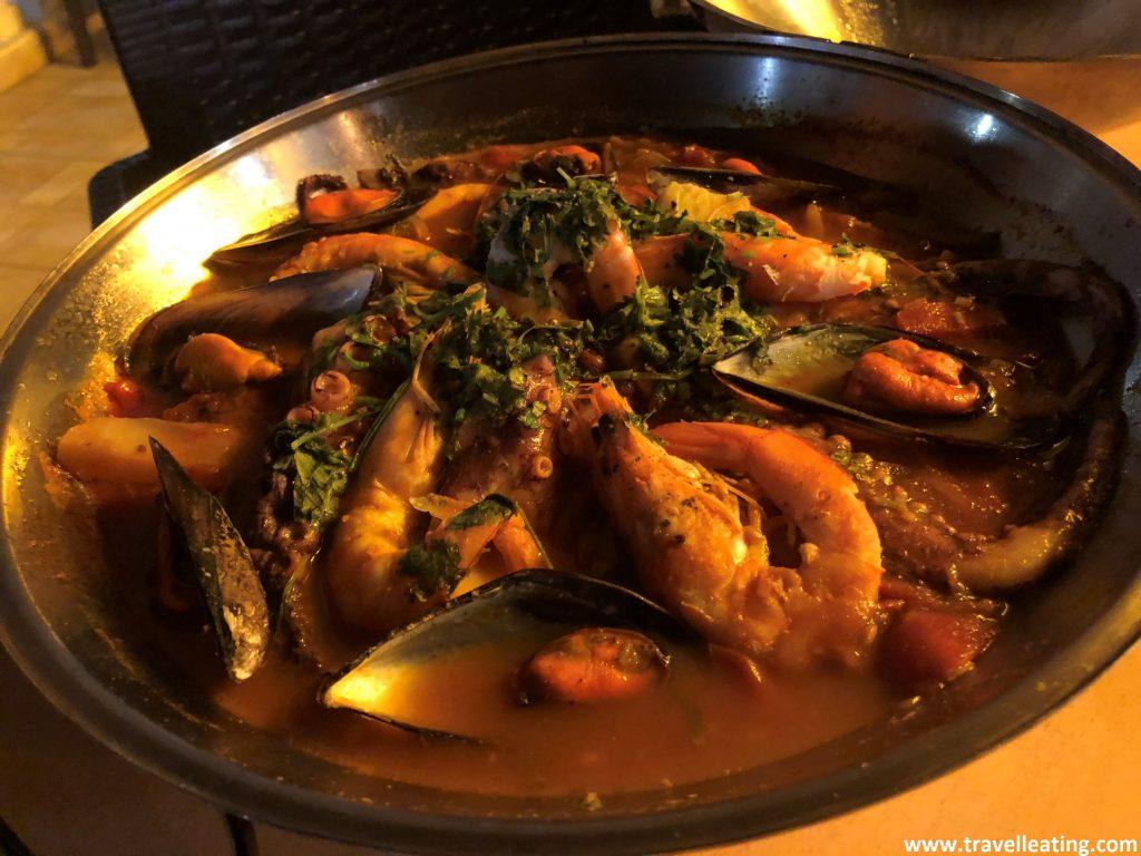 Recipiente redondo que contiene un guiso de pescado y marisco. Se trata de una cataplana, uno de los platos más típicos de Portugal.