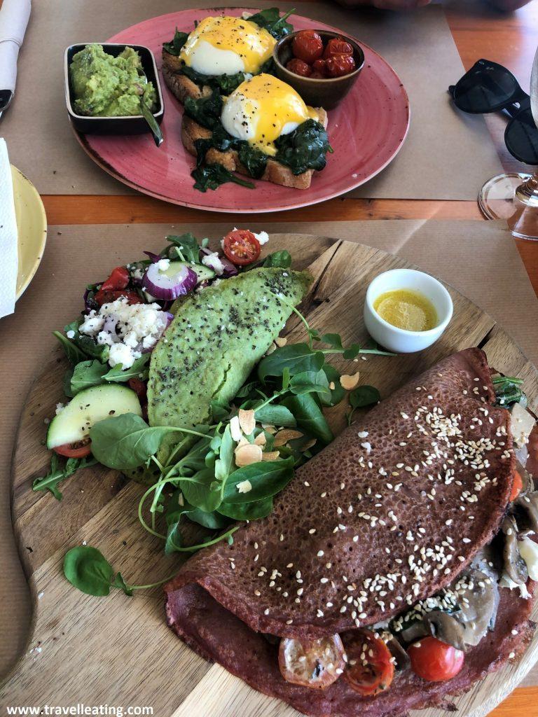 Plato con dos crepes, una verde y una rosada, rellenas de verduras, frente a otro plato que presenta unos huevos benedict servidos con guacamole, espinacas y cherrys asados.