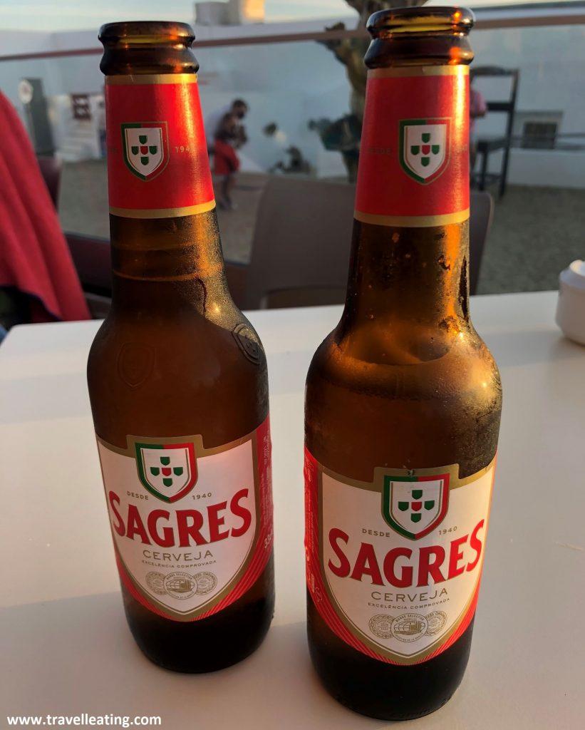 Dos botellas de cerveza Sagres servidas en una mesa blanca.