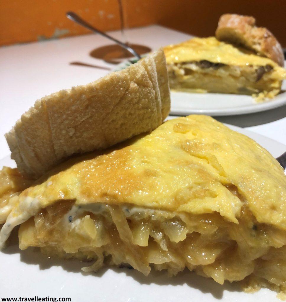 Dos trozos de tortillas rellenas, gruesas, servidas con una rebanada de pan.