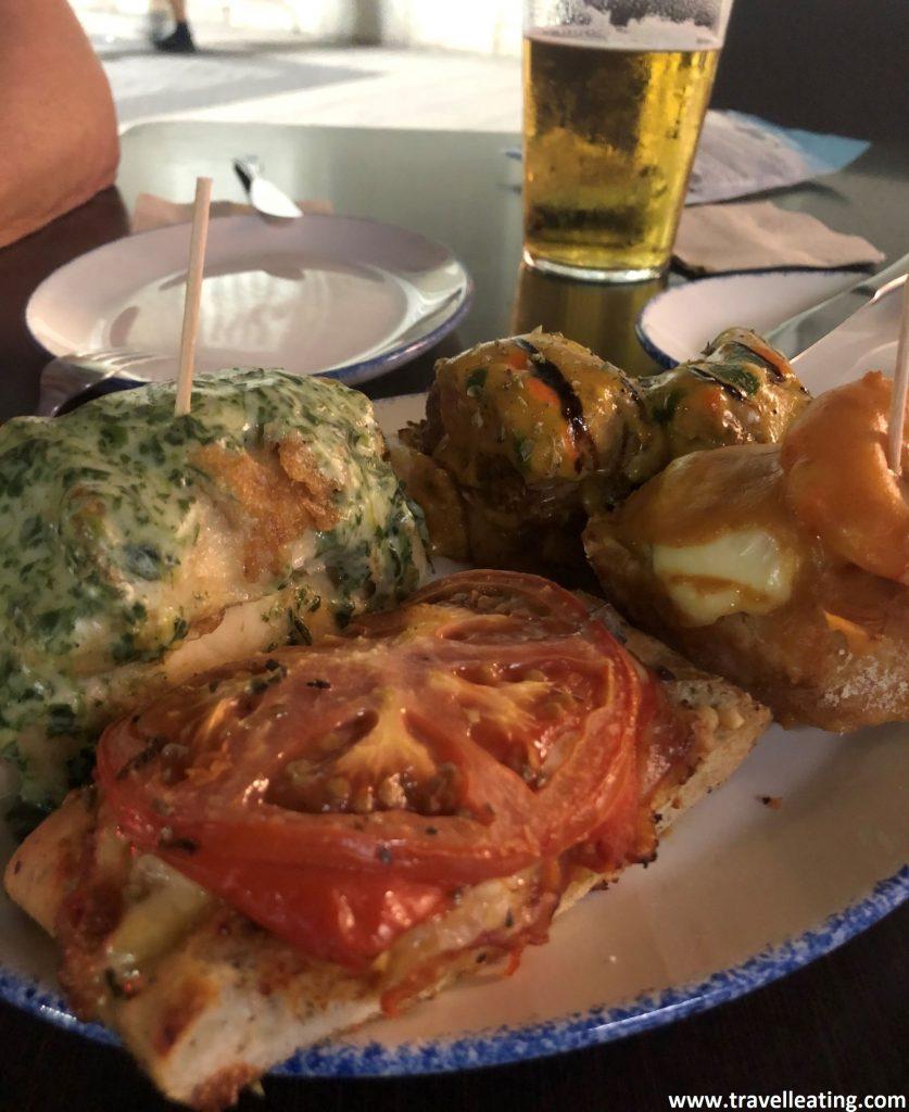 Plato con cinco pinchos: uno de escalivada, un pastel de verduras, otro de pollo al curry, uno de espinacas y otro de langostinos. Servidos en una mesa de terraza de Casa Lita, uno de los mejores restaurantes de Santander.